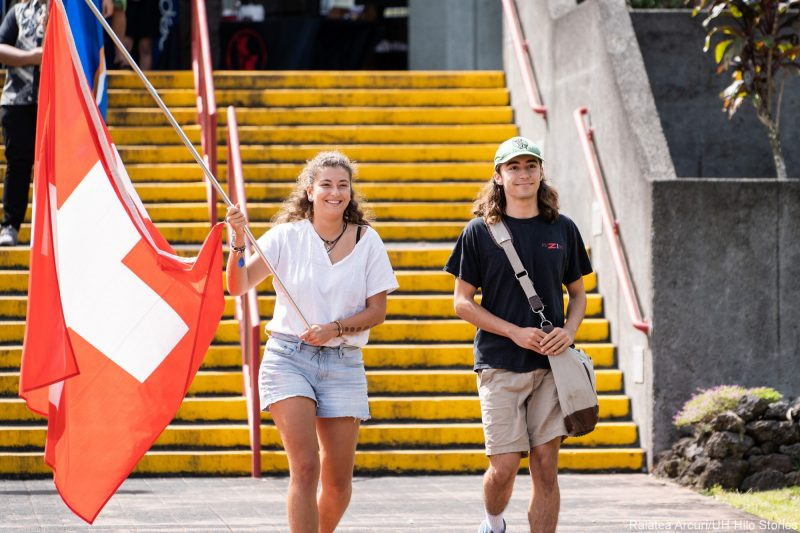 Two students enter venue carrying red and white flag of Switzerland.