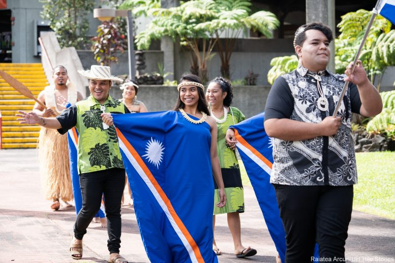 Women in dramatic blue dresses enter venue carrying flag of the Marshall Islands.