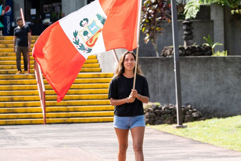 A young woman enters venue carrying orange, white and green flag of Peru.