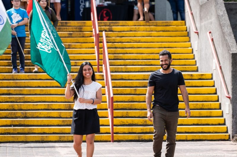 Two students enter venue carrying green flag of Saudi Arabia.