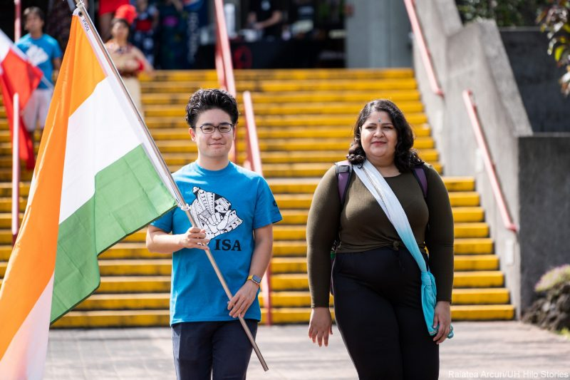 Two students enter venue carrying red, green and red flag of India.