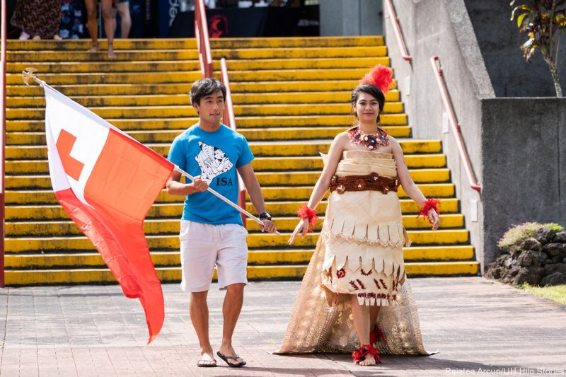 Two students, the young woman in traditional grass skirt and headdress, enter venue carrying red and white flag of Tonga.