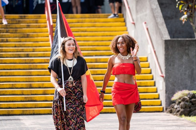 Two young women, one in bright red sarong and top, enter venue carrying red, yellow and black flag of Papua New Guinea.