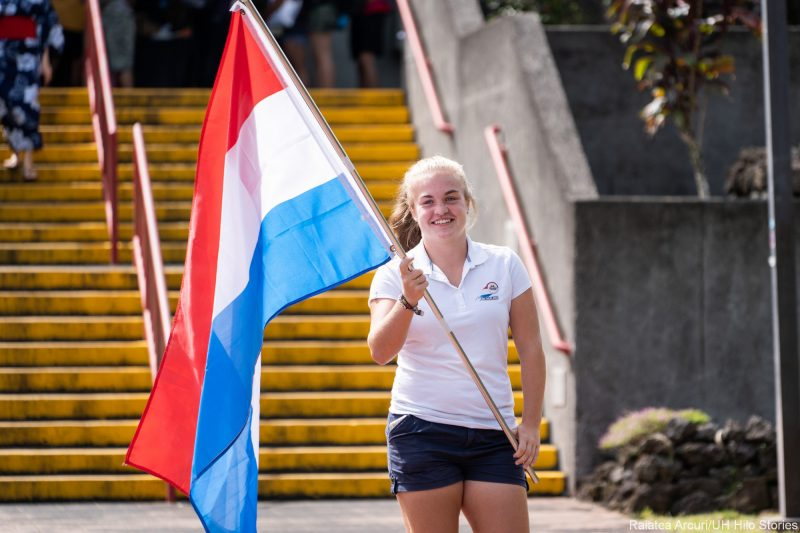 Young woman enters venue carrying red, blue, and white wide striped flag of the Netherlands.
