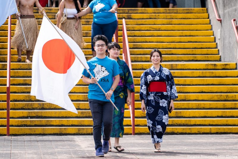 """Group of students enter venue with young man carrying """"rising sun"""" flag of Japan."""