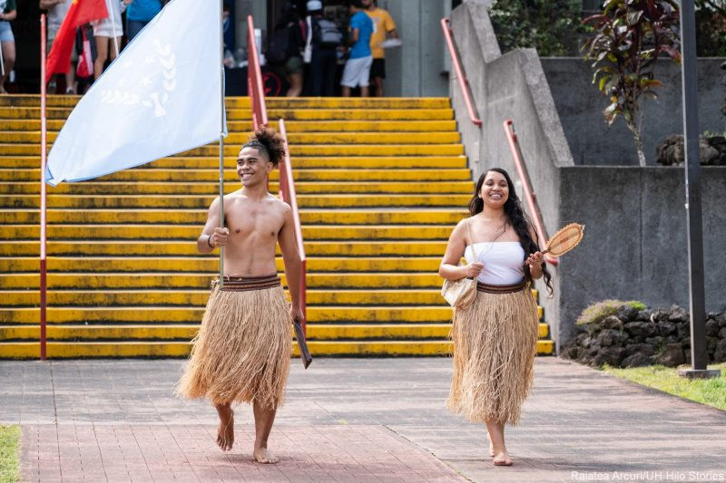 Two students in traditional grass skirts enter venue carrying flag of Kosrae.