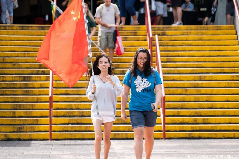 Two young women enter venue carrying the red flag of China.