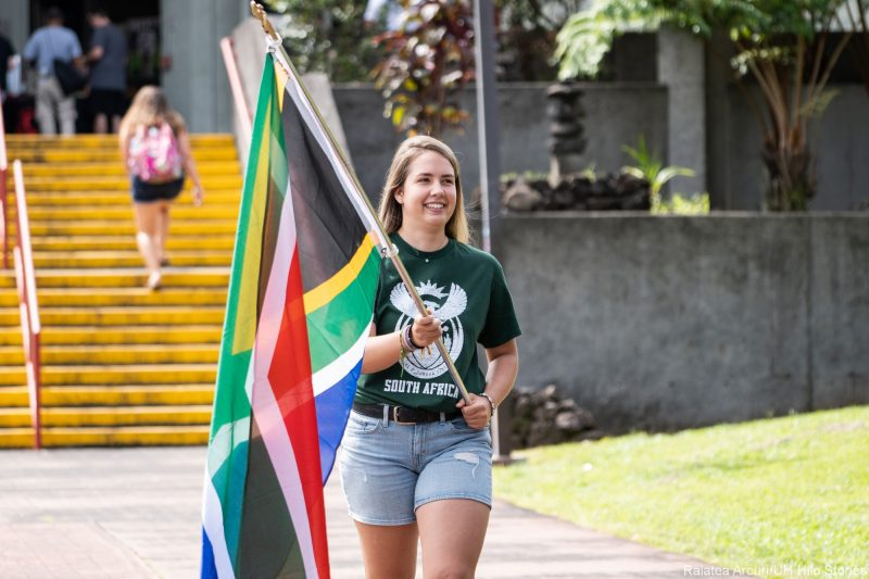 Young woman enters venue carrying colorful flag of South Africa.