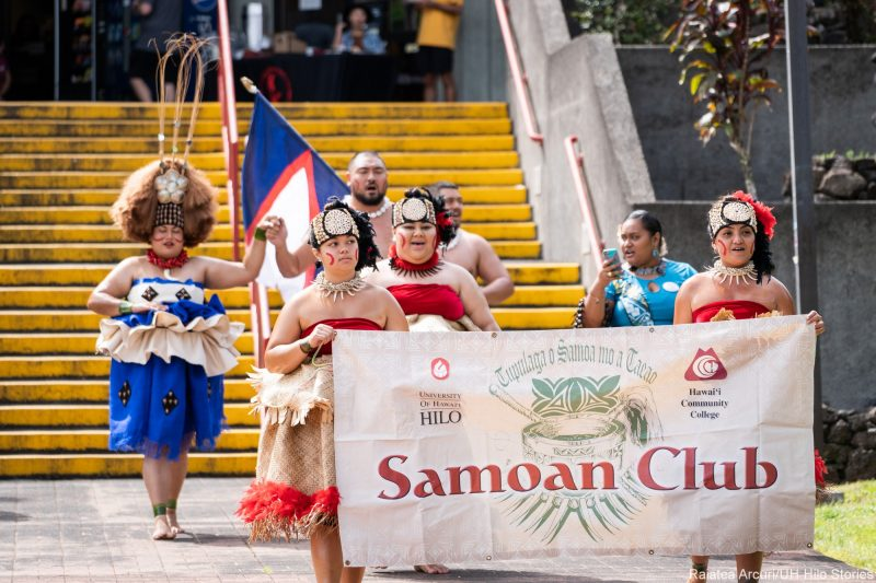 Large group of students enter venue carrying banner with words: Samoan Club. A young man in the rear of the group carried the white, blue and red flag of Samoa.