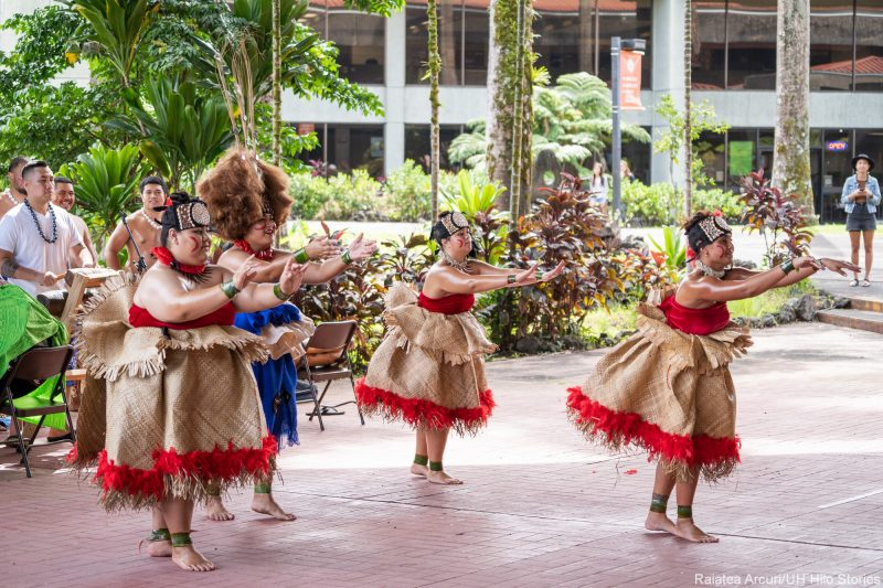 Samoan Club performs group dance. Women are wearing traditional woven skirts.