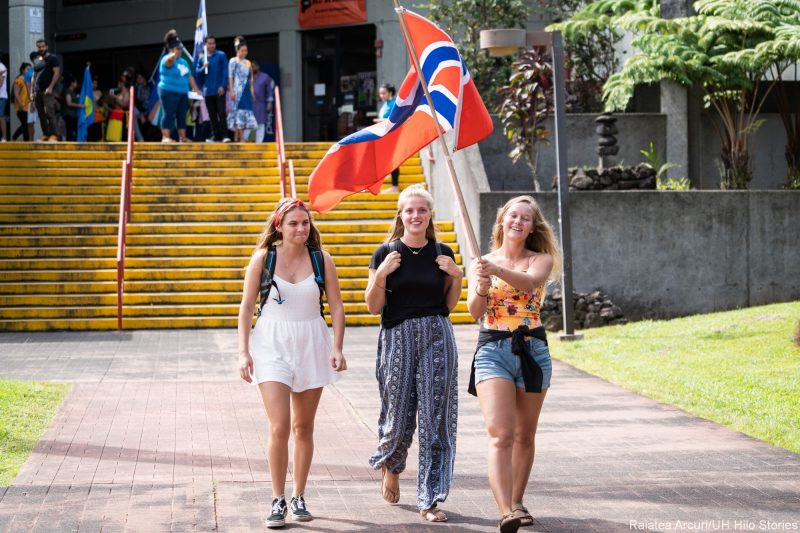 Three young women students enter venue carrying the red, blue and white flag of Norway.