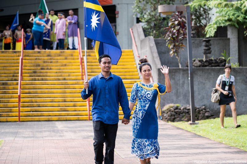 Two students enter venue with Nauru's blue flag with a star burst.