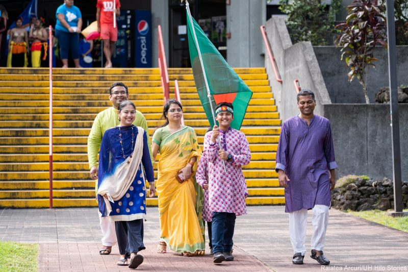 Group of five students enter venue carrying Bangladesh's green and red flag.