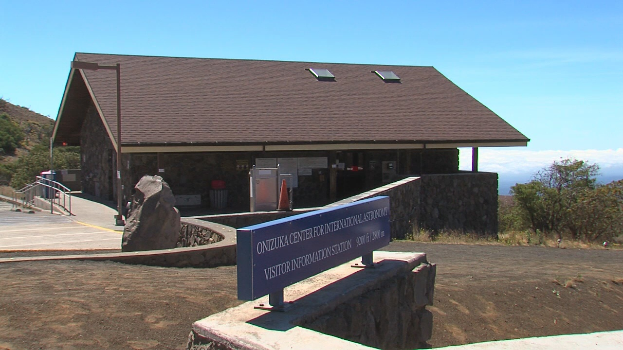 Building made of lava rock, with rock walls surrounding the structure, with the sign: Onizuka Center for International Astronomy, Visitor Information.