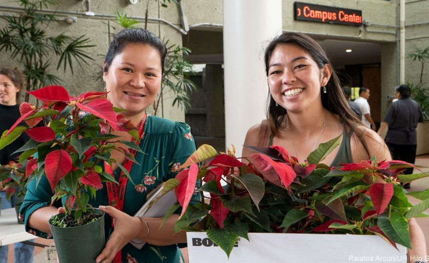 Two customers with poinsettia plants.