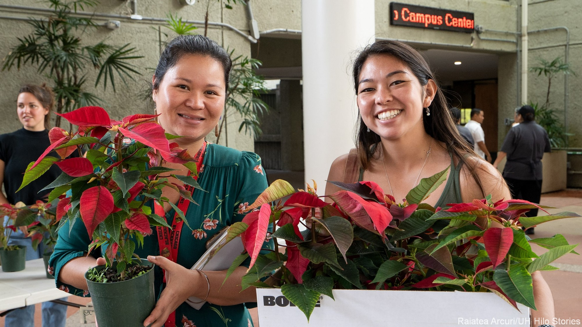 Two women holding poinsettia plants.
