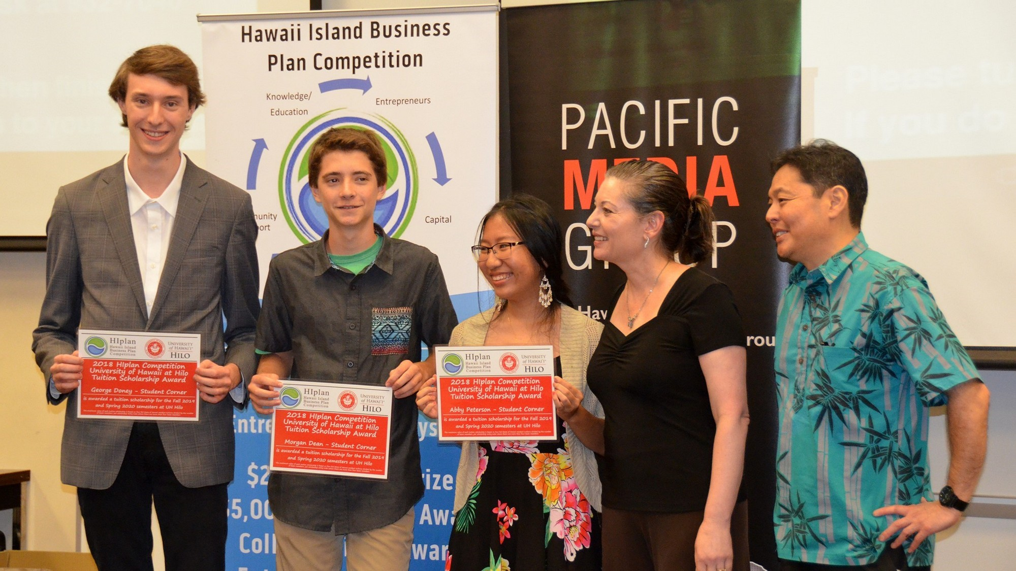 George Donev, Morgan Dean, Abby Peterson, Emmeline DePillis and Jason Ueki pose for group photo. The students are holding certificates for their win. In the back is poster with words: Hawaii Island Business Plan Competition.
