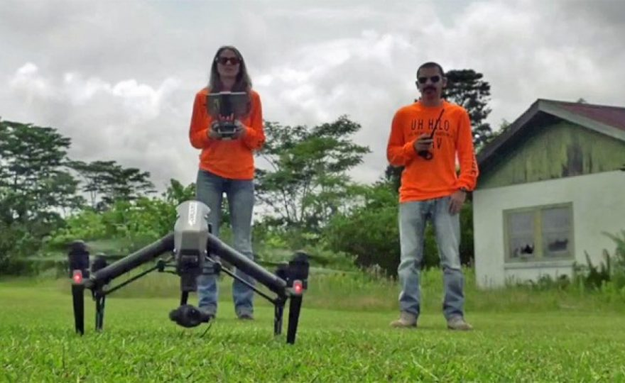 Two drone operators in bright orange t-shirts and holding control equipment for drone, with drone sitting on the lawn just prior to take off.