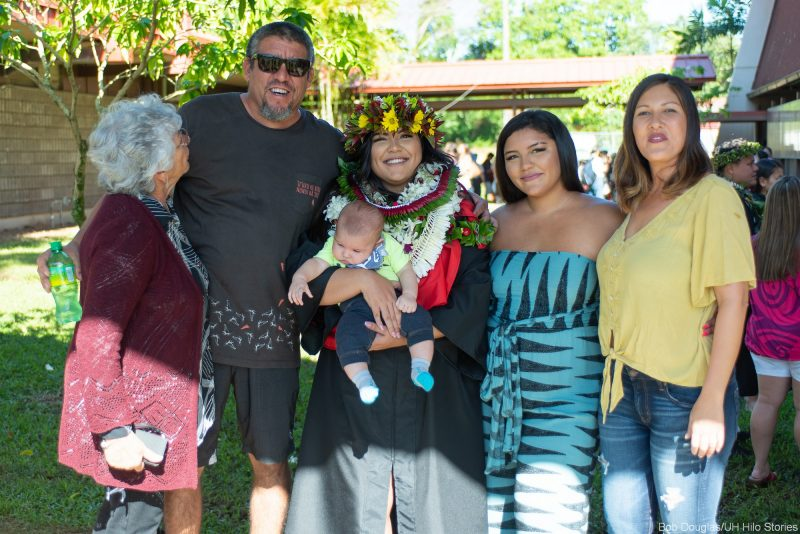 Graduate in lei with family after the ceremonies.