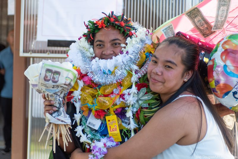 Graduate with lei up to her nose gets a hug.
