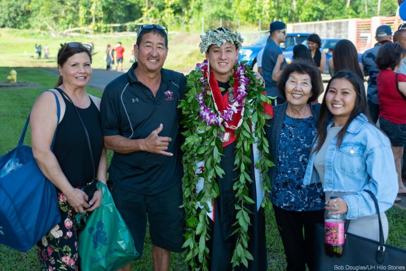 Graduate with family, the shaka from a proud dad.