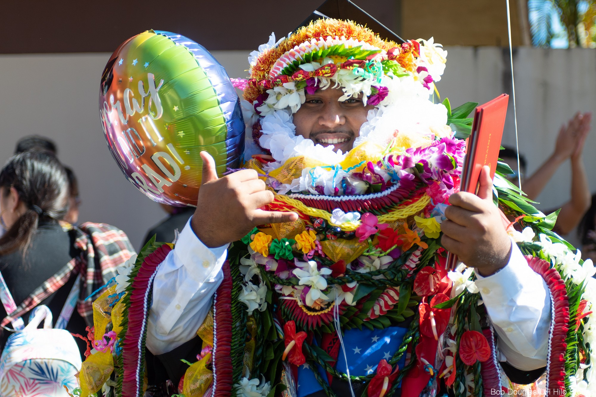 Graduate in lei all the way up to his face. Big smile, holding balloon, giving the shaka.