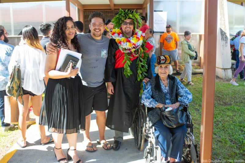 Graduate in lei with family and tutu in wheelchair.