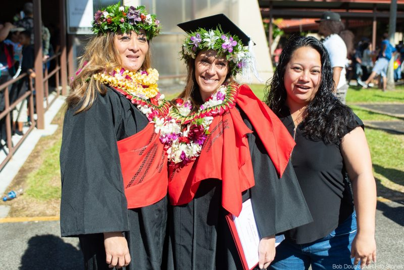 Two female graduates with lei. and red kihei