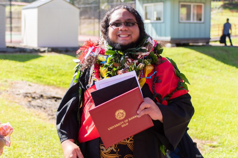 Graduate in lei holding her diploma.