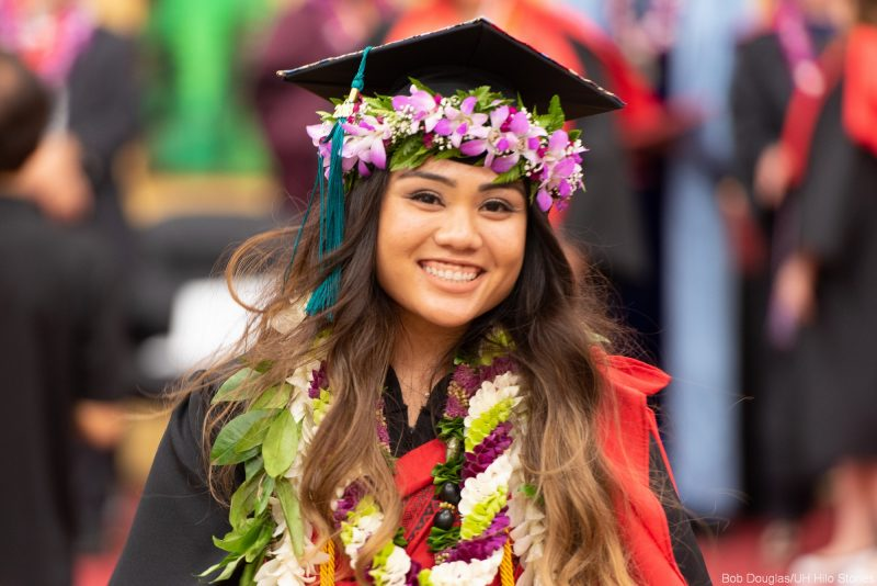 Young woman candidate with orchid head lei around cap.