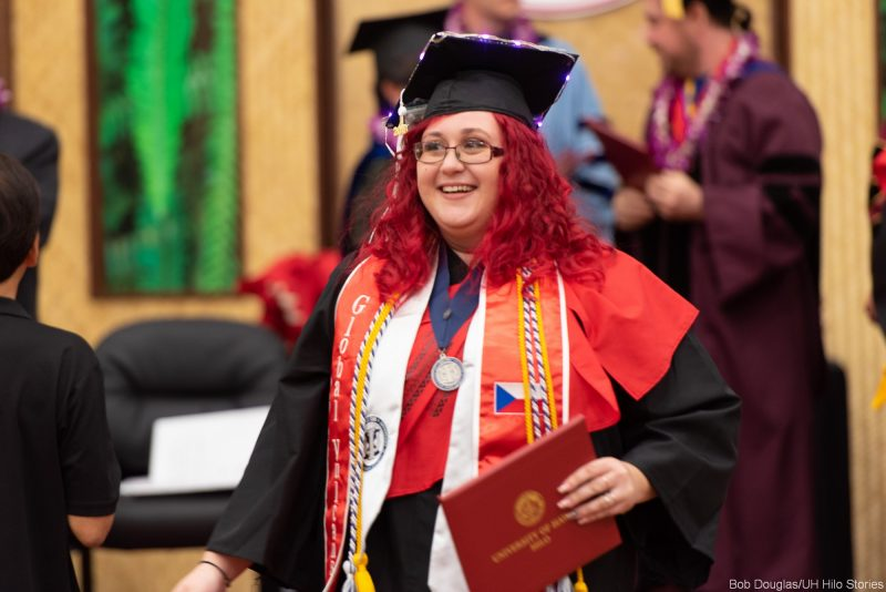 Candidate with bright red hair holds diploma.