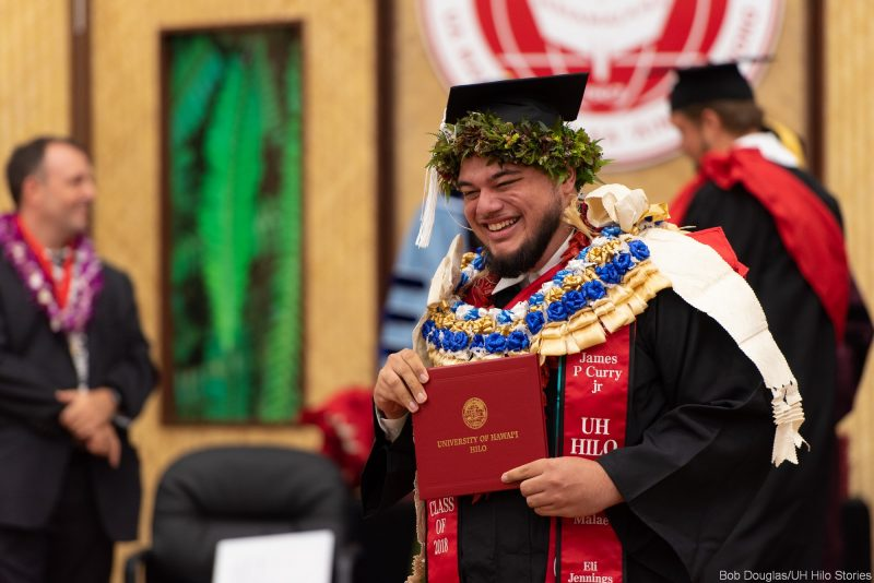 Male candidate with many lei holds his diploma.