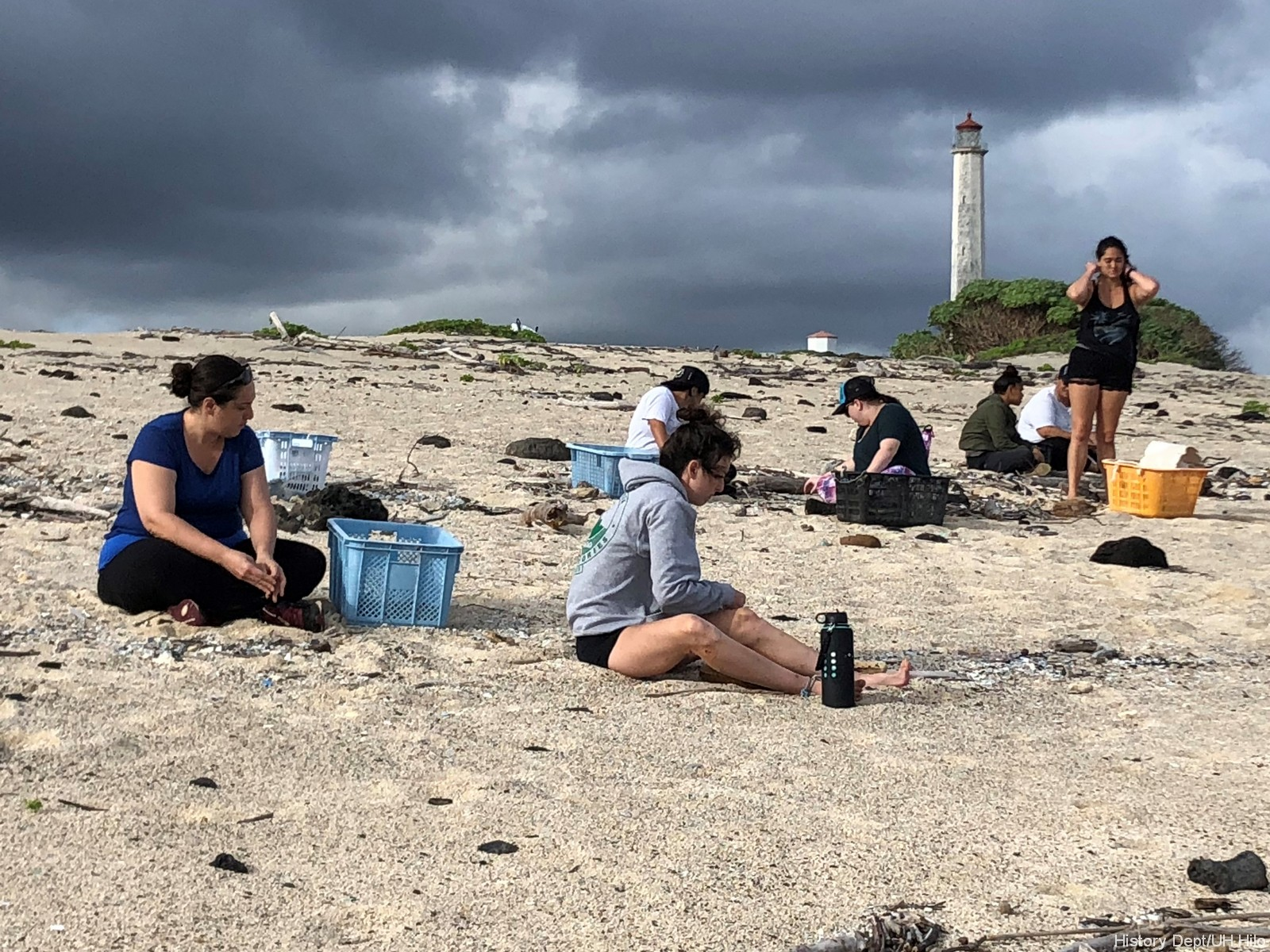 Students seated on beach sifting through sand. Lighthouse is in the background.