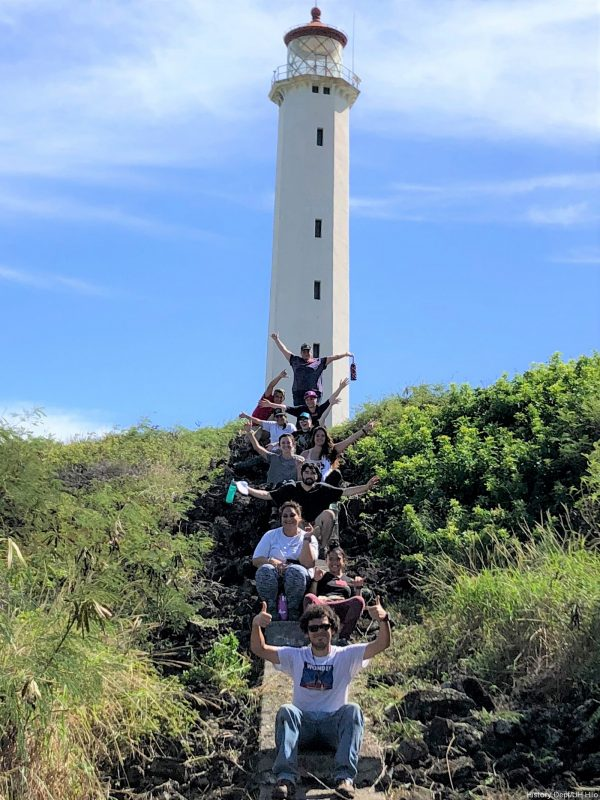 Students sit on step leading up to the lighthouse.