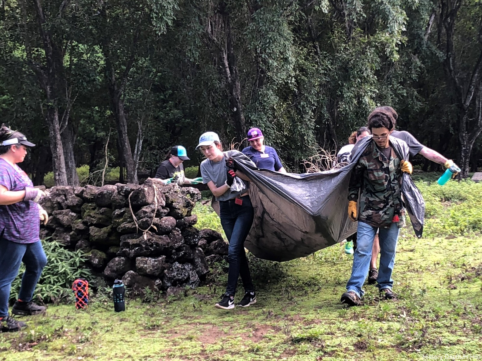 Students haul a large tarp filled with brush they've cleared away.