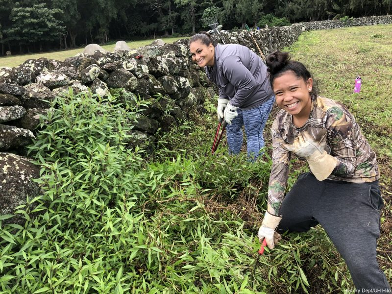 Two women leaning down next to lava rock wall to pull weeds.