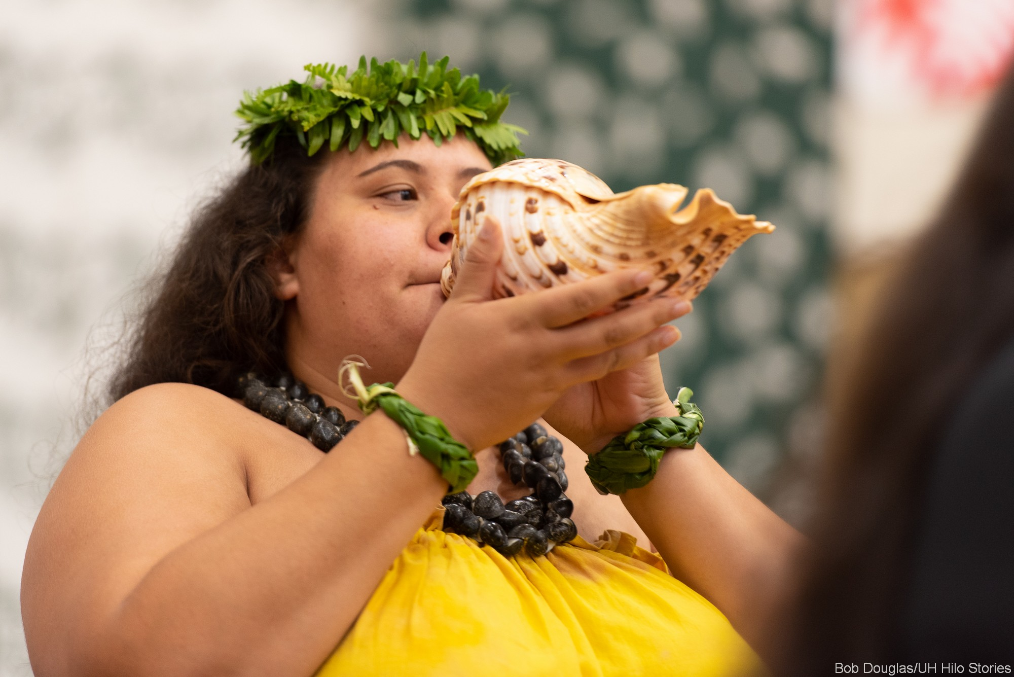 Woman blows conch shell at opening ceremony.