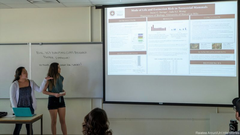 "Jacey Savage and Jade Wong point to their poster presentation on the PowerPoint screen with the title: ""Mode of Life and Extinction Risk in Terrestrial Animals."""