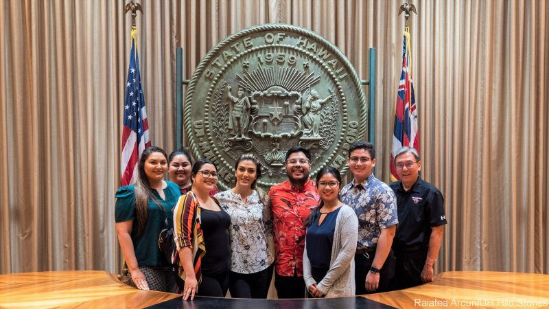 Group stands behind desk used for bill signing with Hawai'i seal and flag plus US flag in background.