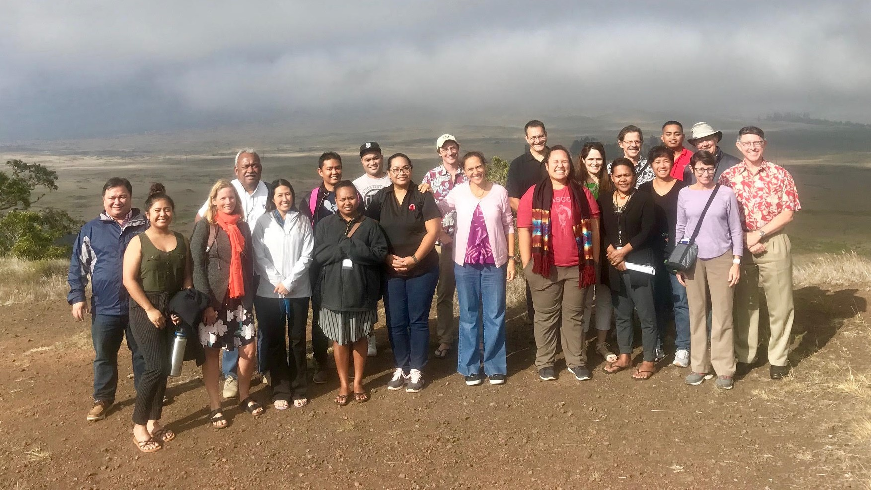Group standing together with Hawai'i Island vista landscape in background.