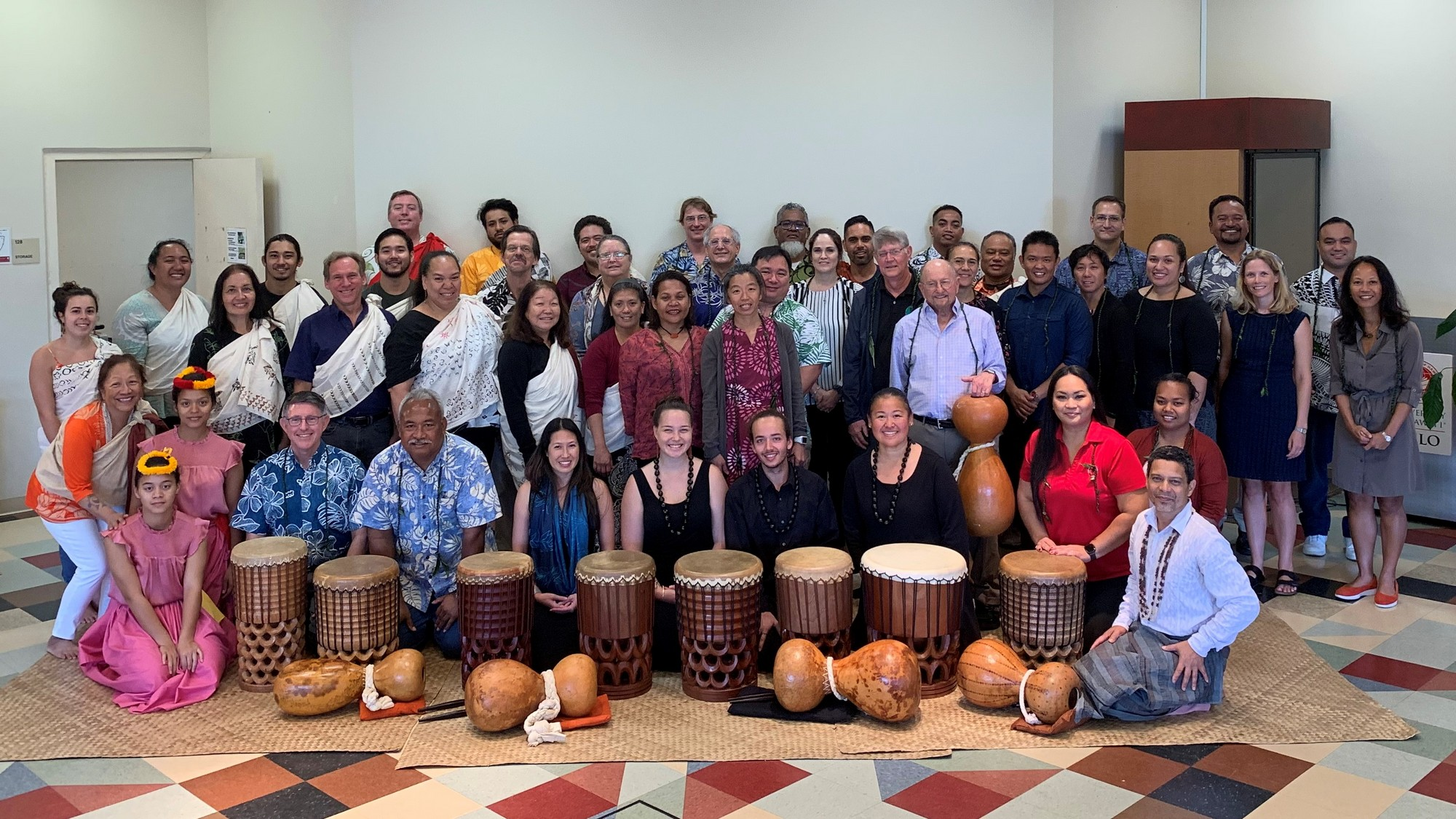 Group photo with delegates and kīpaepae welina participants, group is behind pahu and ipu, standing and sitting on a lauhala mat.
