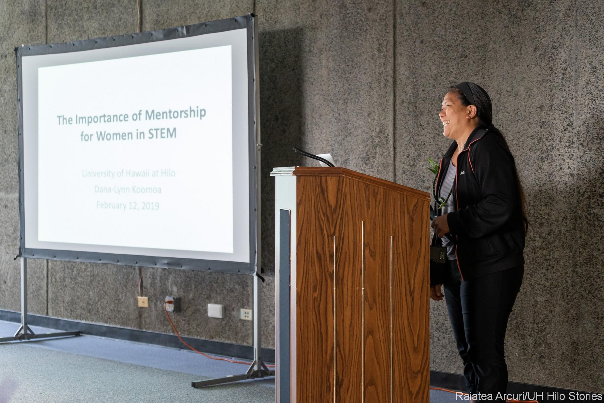 Dana-Lynn Koʻomoa-Lange at podium delivering remarks. On screen topic: The Importance of Mentroship fr Women in STEM