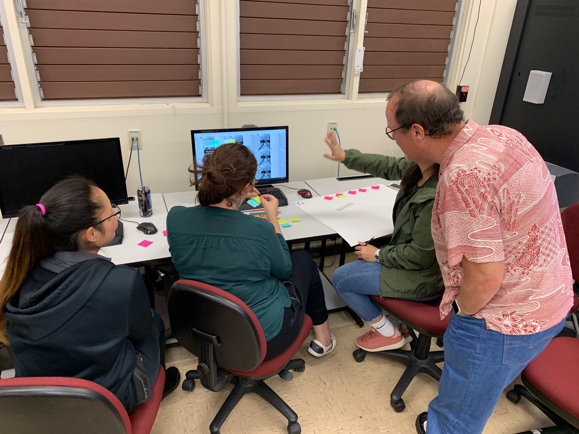 Students at computers with prof. talking to them.