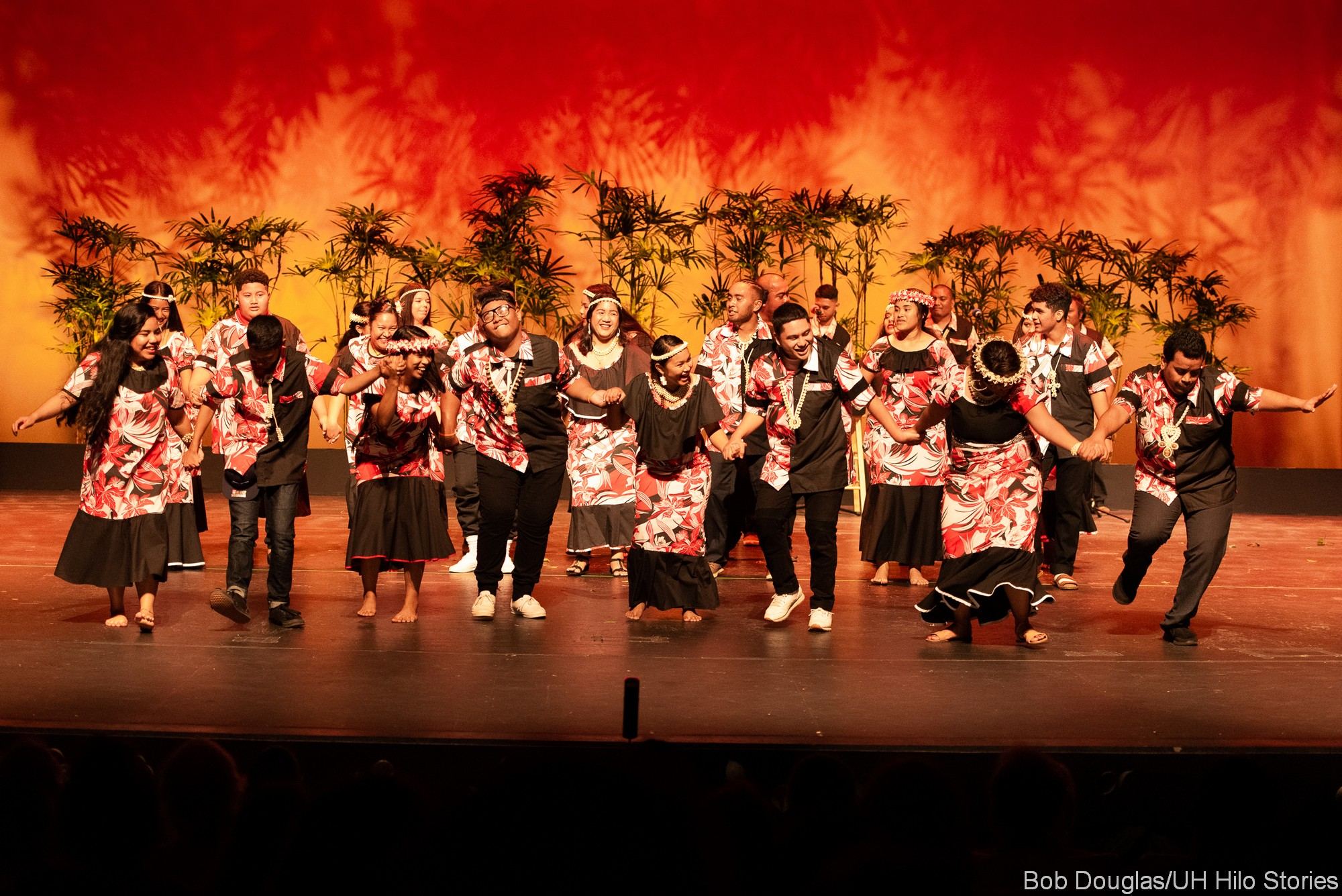 Group dance, black and orange costumes, orange background.