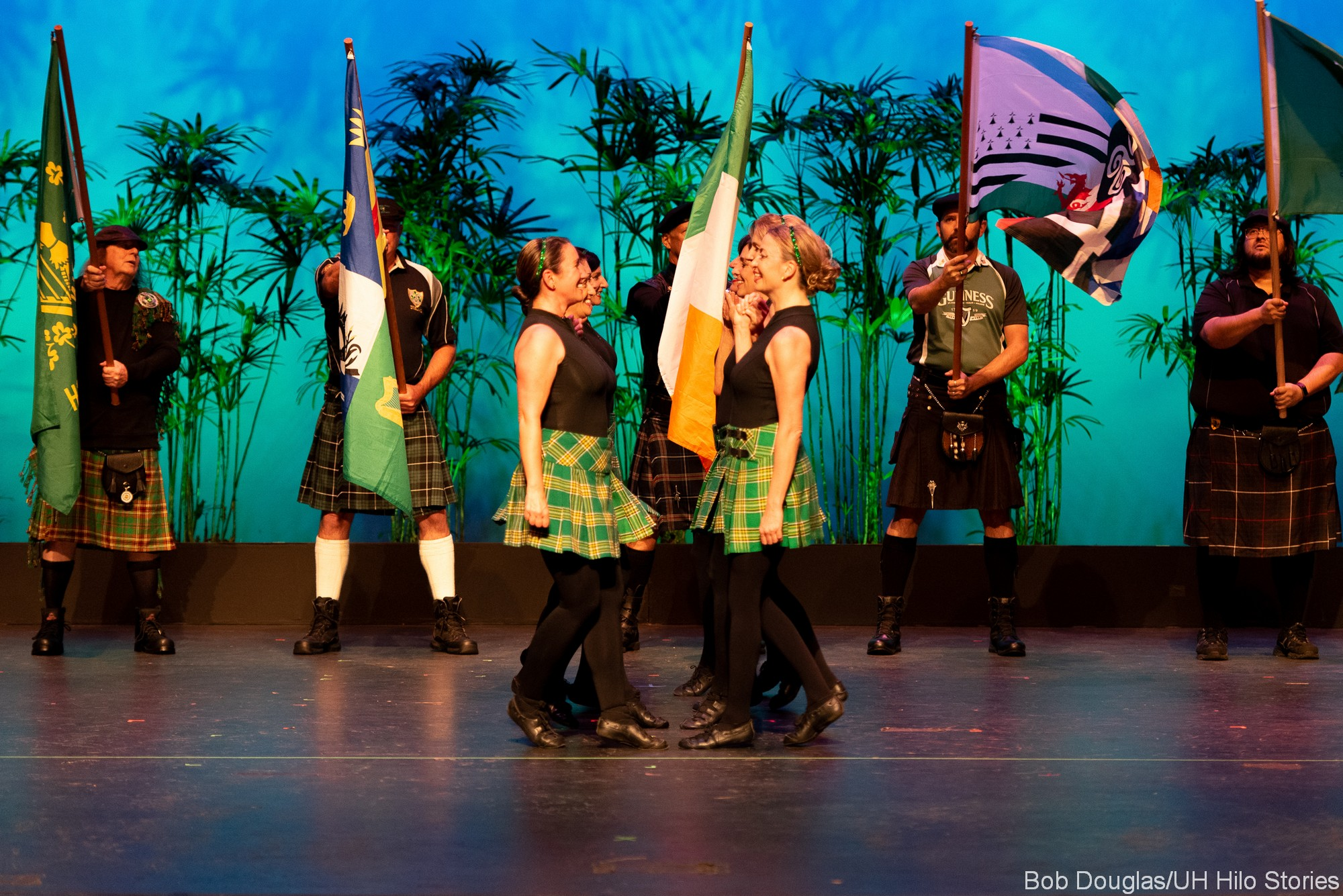 Group of female Irish dancers in traditional dress, plaid skirts, men in background hold flags.