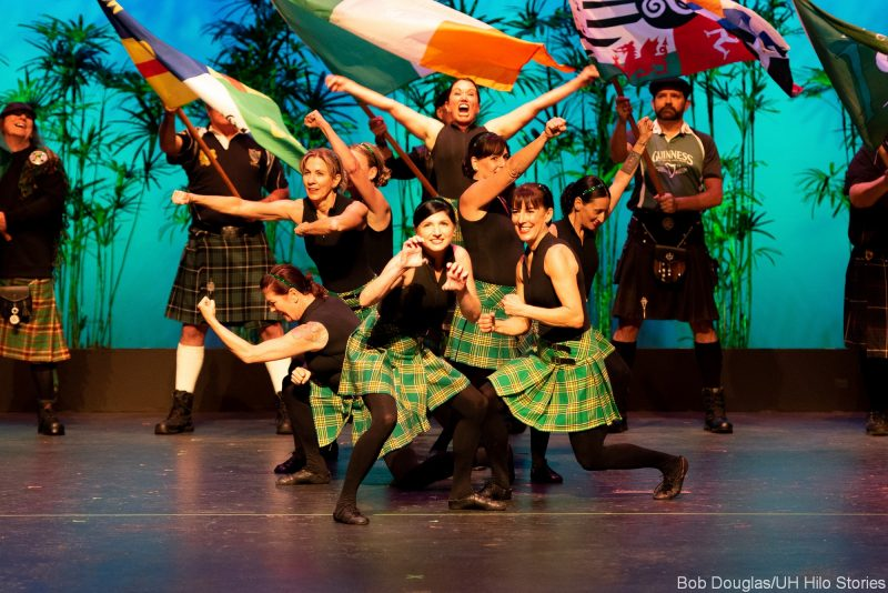 Group of female Irish dancers in traditional dress., with flags.