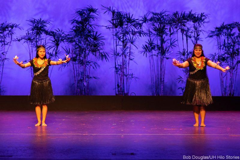 Two women dancing, grass dress.