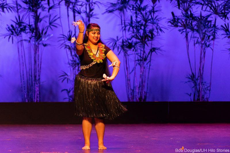Solo woman dancing, grass dress.