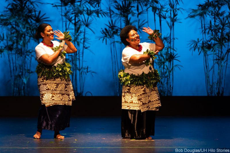 Two female Fijian dancers in traditional dress., hands and arms raised gracefully.