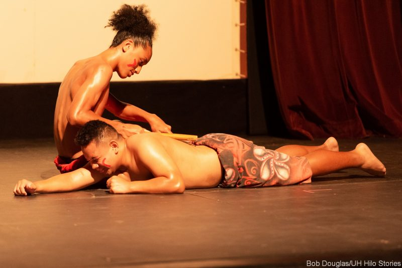Two Samoan dancers, one prone on stage.